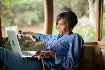 A woman reclines on the coach as she views her retirement accounts on her laptop computer.