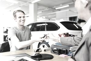 Happy man receiving car keys from saleswoman at desk in showroom