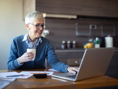 Female senior business woman using laptop at home office