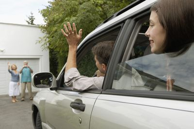 Teen and friends waving at grandparents from inside a vehicle as they back it out of the driveway