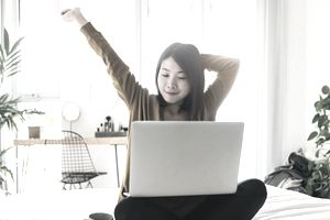 woman stretching while using laptop while sitting cross-legged