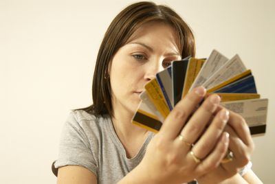 A woman holds multiple credit cards wondering about making a balance transfer