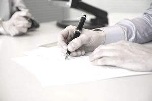 A closeup of a man's hands signing home loan documents