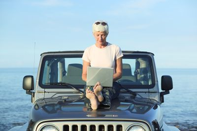 A woman with short hair looks down at a laptop while sitting on the hood of Jeep parked by the ocean