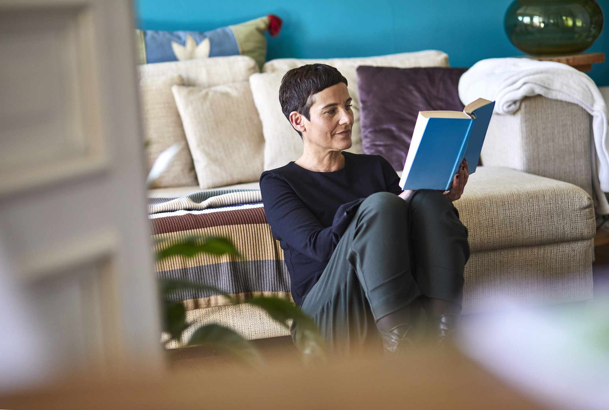 Woman reading book sitting on the floor at home