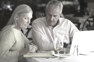 Mature couple writes letter at table in restaurant