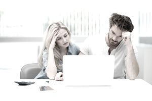 Man and woman worry in front of a laptop