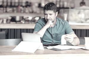 Concerned man at coffee shop looking at laptop with paperwork