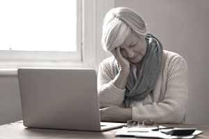 An older woman in front of laptop face in hand with worried look