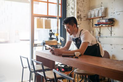 Small business owner working on tablet in a cafe