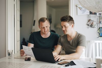 Couple looks at laptop while reviewing a paper bill