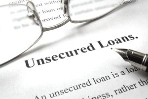 Page of paper with words unsecured loans and glasses.