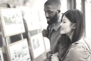 Smiling young couple looking at real estate listings at storefront