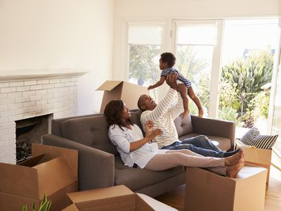 Parents and baby seated on a sofa in a new home surrounded by packing boxes