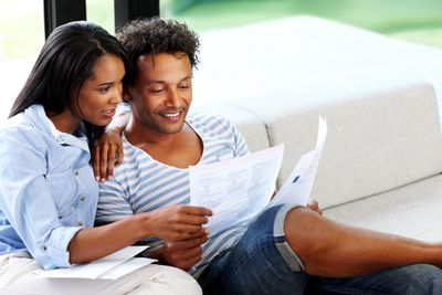 Young couple reading financial and tax paperwork at home.