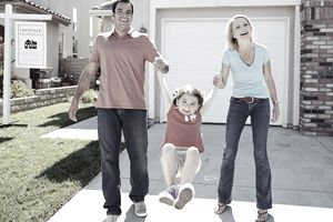 Family swinging daughter (5-7) in front of house