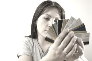A woman holds multiple credit cards in her hand