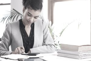Cropped shot of an attractive young businesswoman using a calculator and a notebook while working on her finances in her office