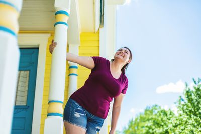 A woman holds a pillar of the front porch of a home.