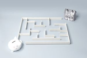 Maze with piggy bank and home model showing the planning needed for home ownership.