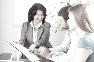 A real estate agent seated at a desk next to a couple, showing them paperwork on a clipboard