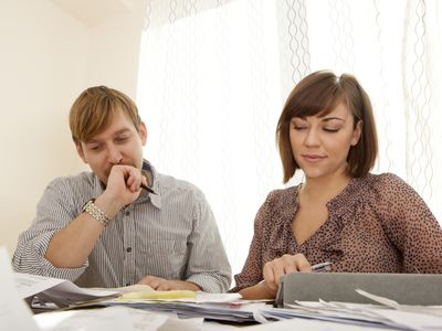 A couple sitting at a table working on taxes together