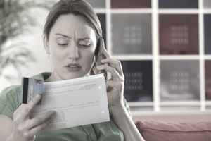woman talking on the phone holding a credit card and document