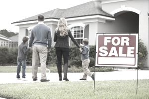Parents with two children approaching a house for sale