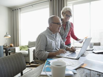 An older couple working together on a laptop.
