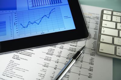 Business graph on a tablet and an itemized expense printout