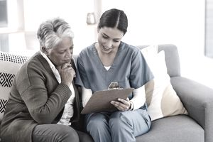 Health-care worker reviewing paperwork with elderly patient