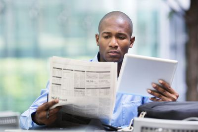 Young man checking the margin debt for stock investments in the newspaper and his his tablet