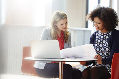 Two businesswomen discussing plans with laptop and paper in bright office