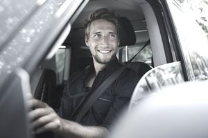 Man smiling and looking out of the window of his car