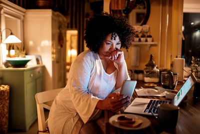 A woman checks her mutual funds on her phone
