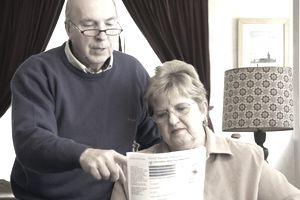 Couple reviewing a social security statement listing benefits available.