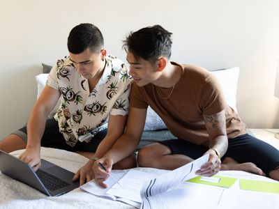 Young couple sits on bed looking at laptop and paperwork