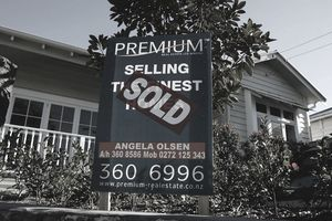 a sold sticker on a for sale sign in front of a house