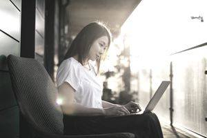 Woman working with computer on her lap, sitting on the balcony at sunset time