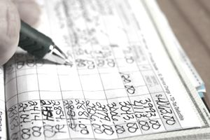 Close-up of someone balancing their checkbook