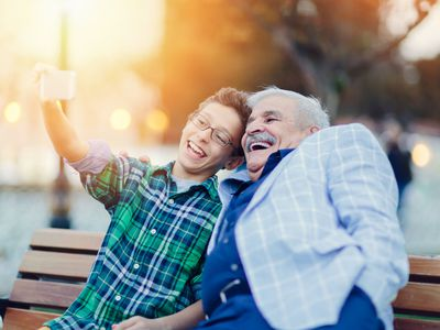 Preteen boy takes selfie with older man on park bench.
