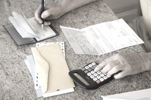Man working at a kitchen counter top using a calculator and writing a check to pay a stack of bills.