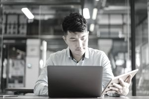 Man working on laptop and tablet