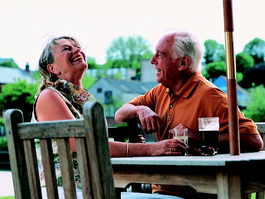 Happy retired couple enjoying drinks knowing their finances are secure