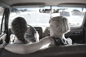 Two young women driving in a car. The passenger has her arm around the driver and is smiling at her.