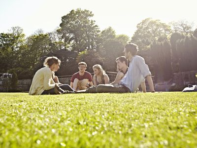 College students have an outdoor discussion on a grassy field during a summer session
