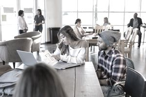 Man reviews paper chart with woman, while seated in cafeteria