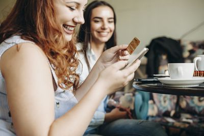 Woman in cafe uses credit card with phone with friend looking on