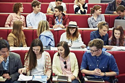 College students sit in a lecture hall talking to each other before class begins