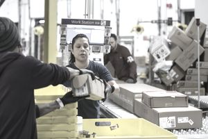 Amazon associates passing merchandise in a fulfillment center, representing productivity.